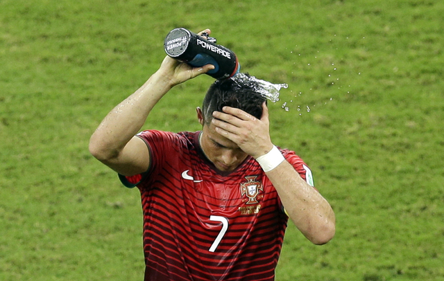 Portugal's Cristiano Ronaldo pours water over his head during the group G World Cup soccer match between the USA and Portugal at the Arena da Amazonia in Manaus, Brazil, Sunday, June 22, 2014. (AP ...
