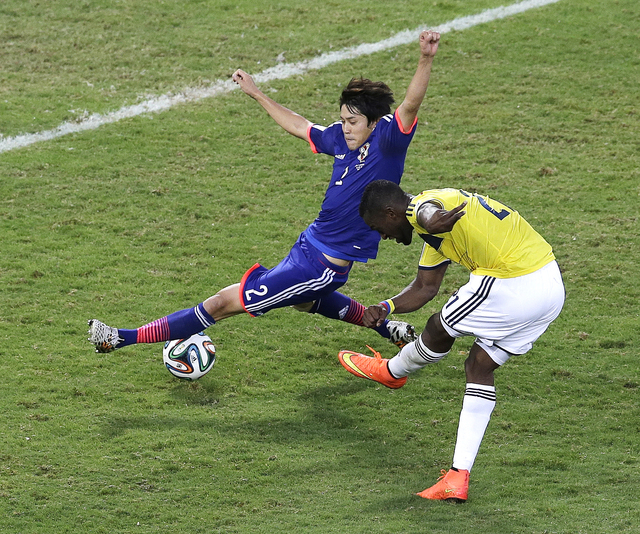 Colombia forward Jackson Martinez, right, scores past Japan defender Atsuto Uchida during the second half of a group C World Cup soccer match at the Arena Pantanal in Cuiaba, Brazil, Tuesday, June ...