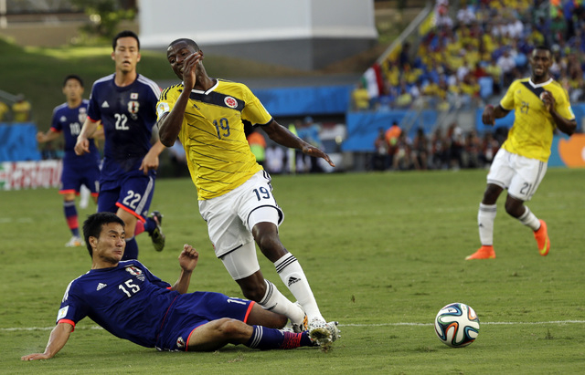 Japan's Yasuyuki Konno fouls Colombia's Adrian Ramos to give away a penalty during the group C World Cup soccer match between Japan and Colombia at the Arena Pantanal in Cuiaba, Brazil, Tuesday, J ...