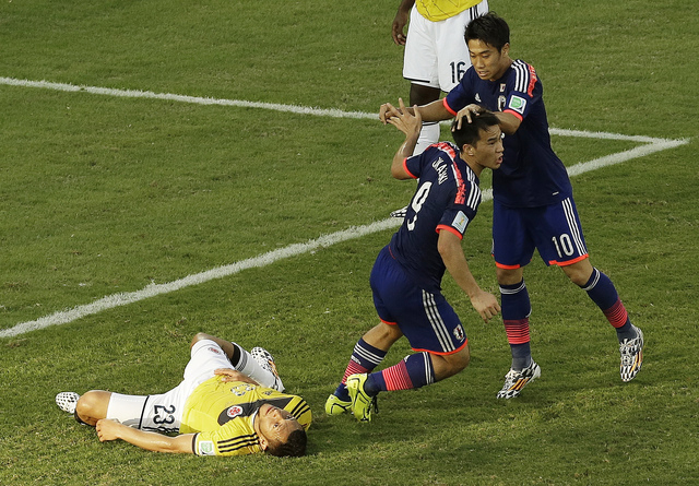 Japan forward Shinji Okazaki, middle, celebrates his goal with Shinji Kagawa, right, past Colombia defender Carlos Valdes during the group C World Cup soccer match between Japan and Colombia at th ...