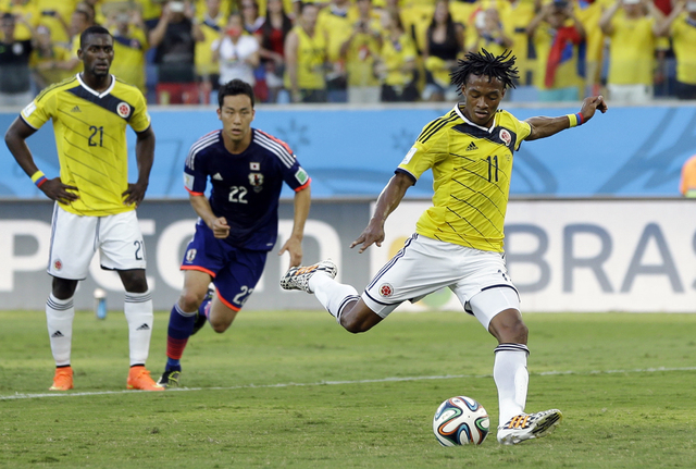 Colombia's Juan Cuadrado scores the opening goal from the penalty spot during the group C World Cup soccer match between Japan and Colombia at the Arena Pantanal in Cuiaba, Brazil, Tuesday, June 2 ...