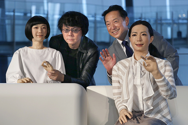 Japanese android expert Hiroshi Ishiguro, second left, and National Museum of Emerging Science and Innovation Miraikan Chief Executive Director Mamoru Mohri, second right, pose with a female-annou ...