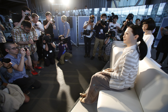 Photographers gather around to take photos of a female-announcer robot called Otonaroid, second right, and a girl robot called Kodomoroid, right, during a press unveiling of new guides at the Nati ...
