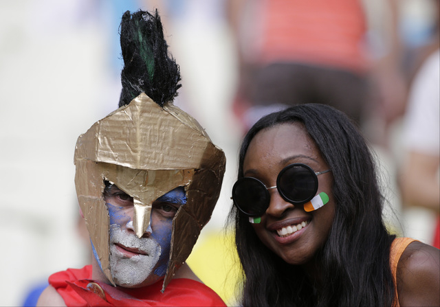 A Greece and an Ivory Coast supporter pose for a photograph prior to the group C World Cup soccer match between Greece and Ivory Coast at the Arena Castelao in Fortaleza, Brazil, Tuesday, June 24, ...