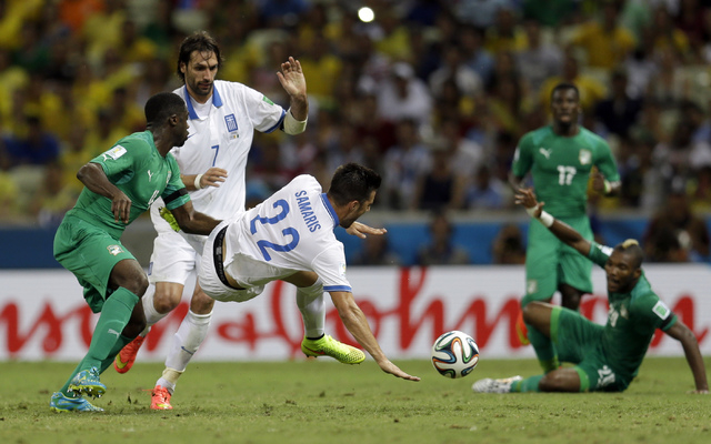 Greece's Andreas Samaris, center, is tackled by Ivory Coast's Kolo Toure, left, during the group C World Cup soccer match between Greece and Ivory Coast at the Arena Castelao in Fortaleza, Brazil, ...