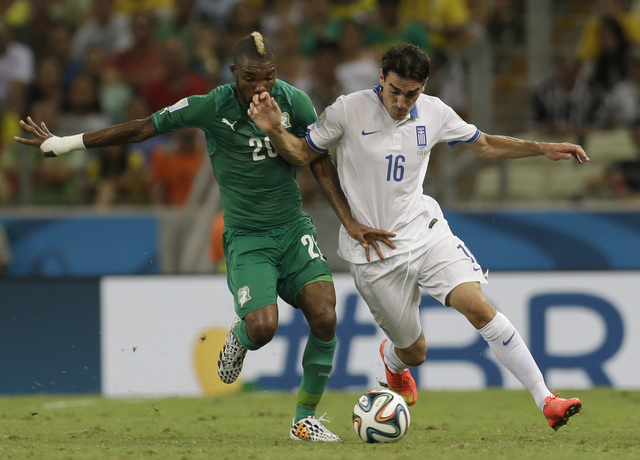 Ivory Coast's Serey Die, left, and Greece's Lazaros Christodoulopoulos challenge for the ball during the group C World Cup soccer match between Greece and Ivory Coast at the Arena Castelao in Fort ...