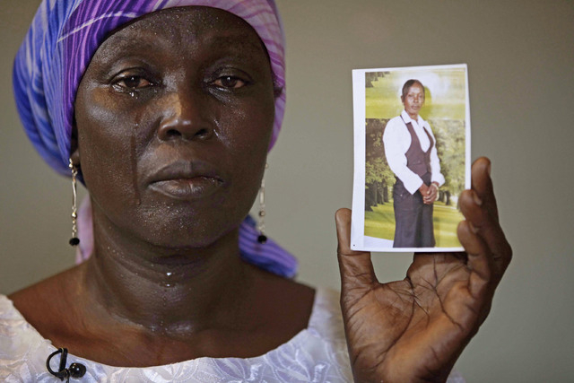 In this Monday, May 19, 2014 file photo, Martha Mark, the mother of kidnapped school girl Monica Mark, cries as she display her photo in the family house, in Chibok, Nigeria. Islamic extremists ha ...