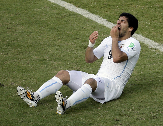 Uruguay's Luis Suarez reacts while sitting on the pitch during the group D World Cup soccer match between Italy and Uruguay at the Arena das Dunas in Natal, Brazil, Tuesday, June 24, 2014. (AP Pho ...