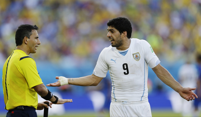 Uruguay's Luis Suarez argues with referee Marco Rodriguez from Mexico during the group D World Cup soccer match between Italy and Uruguay at the Arena das Dunas in Natal, Brazil, Tuesday, June 24, ...