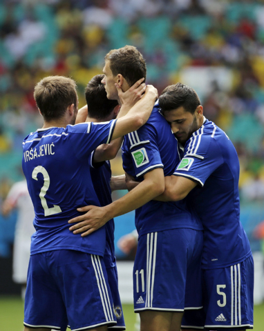 Bosnia's Edin Dzeko, center, is greeted by his teammates after scoring the opening goal during a group F World Cup soccer match between Bosnia and Iran at the Arena Fonte Nova in Salvador, Brazil, ...