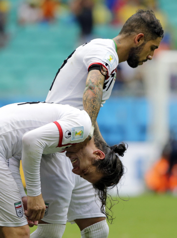 Iran's Ashkan Dejagah, top, consoles Iran's Andranik Teymourian after the group F World Cup soccer match between Bosnia and Iran at the Arena Fonte Nova in Salvador, Brazil, Wednesday, June 25, 20 ...