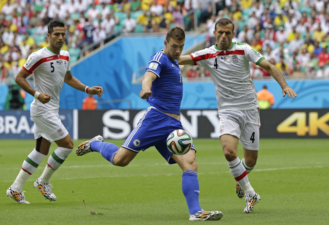 Bosnia's Edin Dzeko, center, gets in a shot despite the challenge of Iran's Jalal Hosseini, right, during the group F World Cup soccer match between Bosnia and Iran at the Arena Fonte Nova in Salv ...