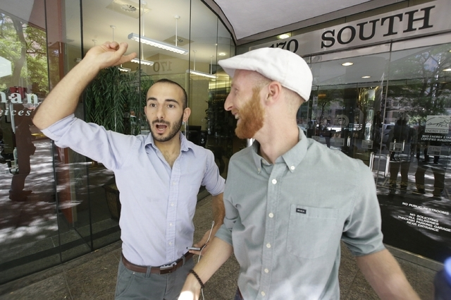 Plaintiffs Moudi Sbeity, left, and his partner Derek Kitchen, one of three couples who brought a lawsuit against Utah's gay marriage ban, celebrate as they arrive at their lawyer's office in Salt  ...