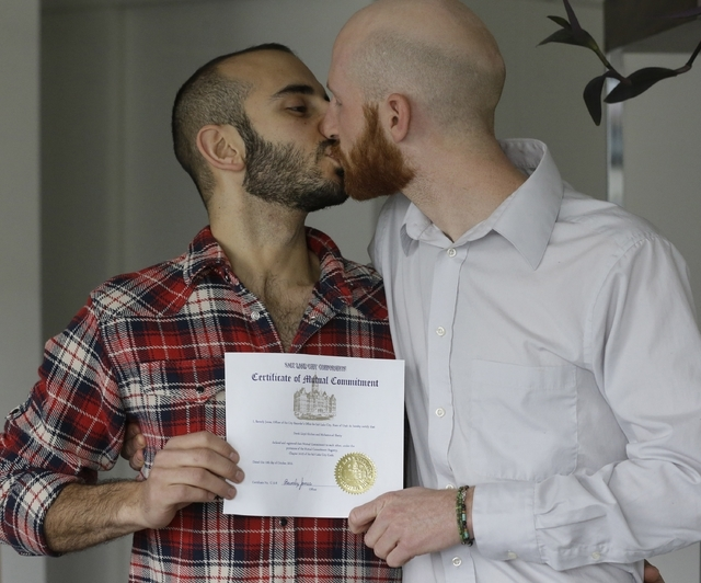 In this April 3, 2014, file photo, Derek Kitchen, right, and Moudi Sbeity kiss as they hold their certificate of mutual commitment at their home, in Salt Lake City. (AP Photo/Rick Bowmer, File)