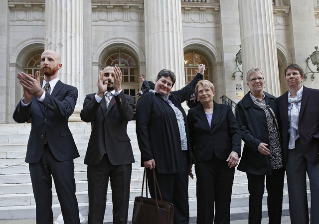 In this April 10, 2014 file photo, the plaintiffs challenging Utah's gay marriage ban, from left, Derek Kitchen and his partner, Moudi Sbeity; Kate Call, her partner, Karen Archer; Laurie Wood and ...