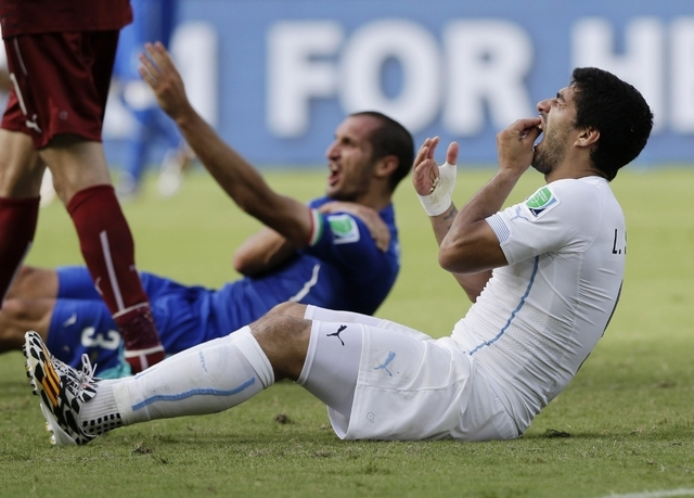 10ThingstoSeeSports - Uruguay's Luis Suarez holds his teeth after running into Italy's Giorgio Chiellini's shoulder during the group D World Cup soccer match between Italy and Uruguay at the Arena ...
