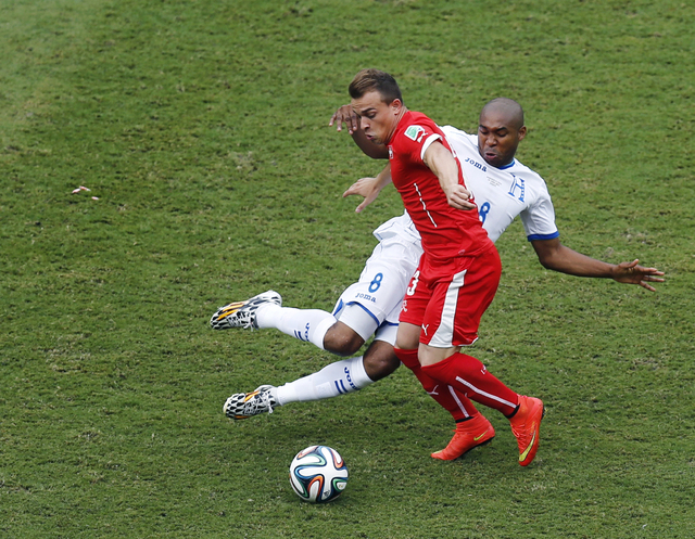 Switzerland's Xherdan Shaqiri and Honduras' Wilson Palacios (8) challenge for the ball during the group E World Cup soccer match between Honduras and Switzerland at the Arena da Amazonia in Manaus ...