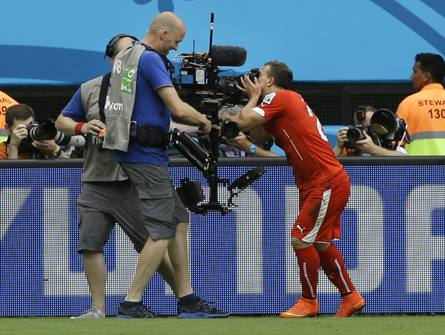 Switzerland's Xherdan Shaqiri kisses a TV camera as he celebrates after scoring the opening goal during the group E World Cup soccer match between Honduras and Switzerland at the Arena da Amazonia ...