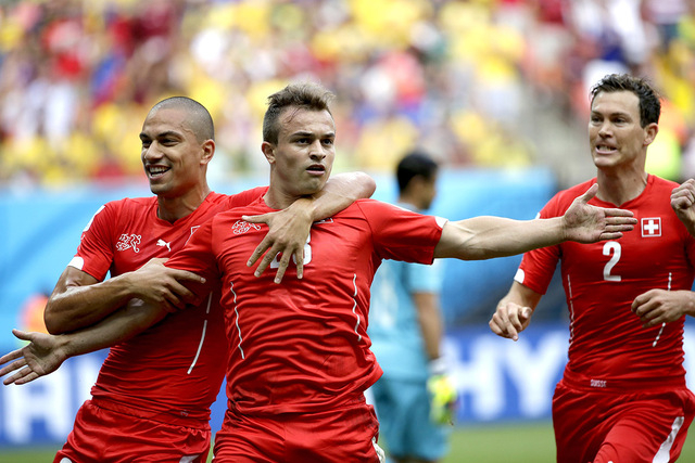 Switzerland's Xherdan Shaqiri, center, celebrates with teammate  Goekhan Inler, left, and Stephan Lichtsteiner (2) after scoring during the group E World Cup soccer match between Honduras and Swit ...