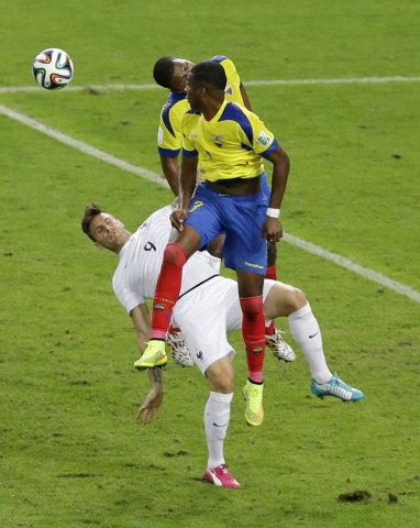 Ecuador's Frickson Erazo, center, and Jorge Guagua, right, both attempt to head the ball over France's Olivier Giroud during the group E World Cup soccer match between Ecuador and France at the Ma ...