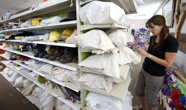 Katie Cornelius, the volunteer exhibit curator for the Tribute Fence Preservation Project, looks through a section of hats among the thousands of artifacts saved from the tribute honoring the 19 G ...