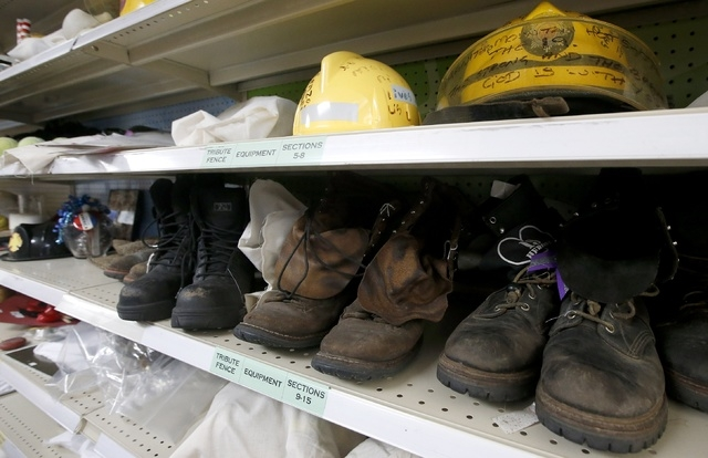 Old wildfire fire fighting gear once part of a makeshift memorial, are just some of the thousands of artifacts carefully cataloged and saved for the Tribute Fence Preservation Project honoring the ...