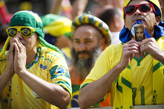 Fans of Brazil pray before a live broadcast of the World Cup round of 16 soccer match between Brazil and Chile, inside the FIFA Fan Fest area in Sao Paulo, Brazil, Saturday, June 28, 2014. (AP Pho ...