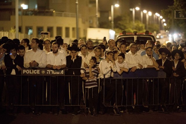 Orthodox Jews, family and friends of Israeli Eyal Yifrah, 19, one of three missing teenagers, gather out side of his home in Elad, central Israel, Monday, June 30, 2014. The Israeli military found ...