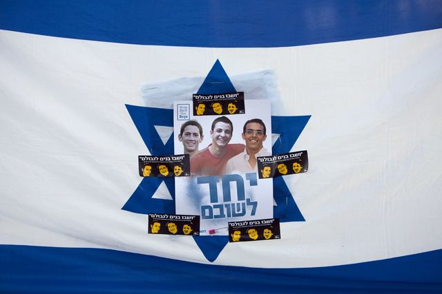 Israelis hold the national flag on Sunday, June 29, 2014, with photos of the three missing Israeli teens feared abducted in the West Bank on June 12, during a rally calling for their release, in T ...