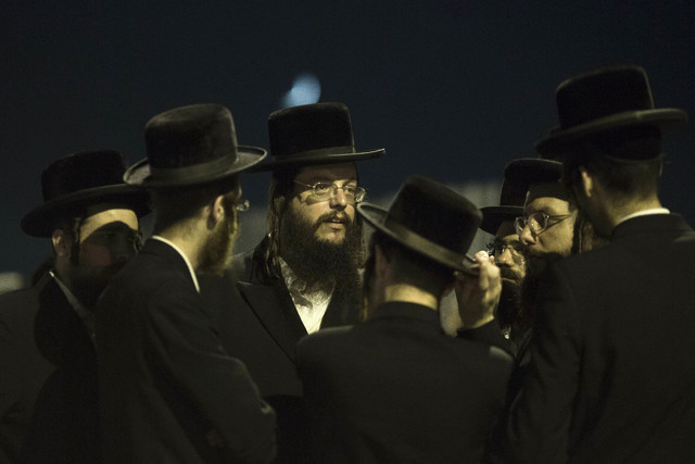 Orthodox Jews, family and friends of Israeli Eyal Yifrah, 19, one of three missing teenagers, gather outside of his home in Elad, central Israel, Monday, June 30, 2014. The Israeli military found  ...