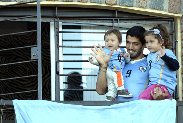 Uruguay's soccer player Luis Suarez, center, with his children Benjamin, left, and Delfina, waves to fans from his home, before the start of his team's World Cup round 16 match with Colombia, on t ...