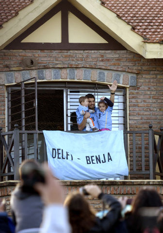 Uruguay's soccer player Luis Suarez, with his children Benjamin, left, and Delfina, waves to fans from his home, before the start of his team's World Cup round 16 match with Colombia, on the outsk ...