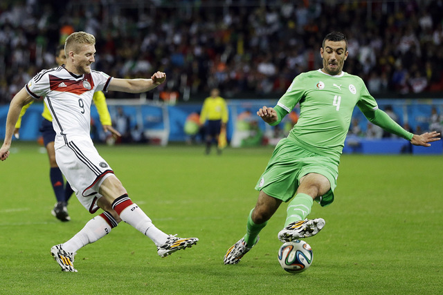 Germany's Andre Schuerrle, left, takes a shot past Germany's Benedikt Hoewedes during the World Cup round of 16 soccer match between Germany and Algeria at the Estadio Beira-Rio in Porto Alegre, B ...