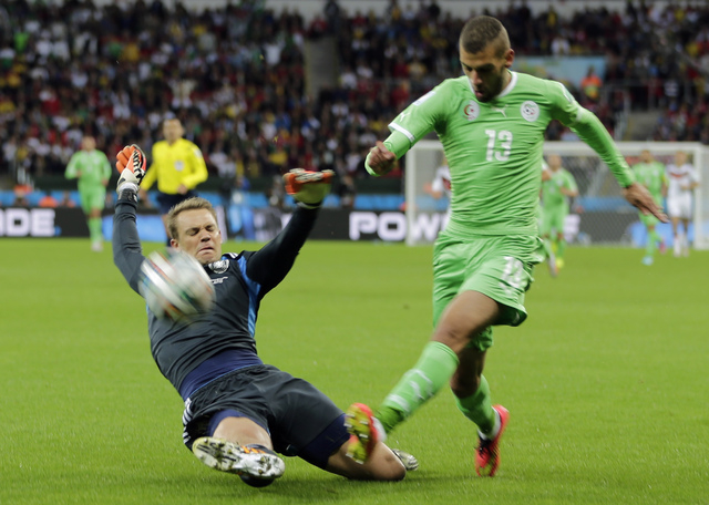 Germany's goalkeeper Manuel Neuer, left, slides in to make a save against Algeria's Islam Slimani during the World Cup round of 16 soccer match between Germany and Algeria at the Estadio Beira-Rio ...