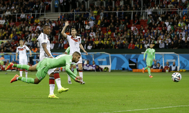 Algeria's Islam Slimani is airborne in front of Germany's Jerome Boateng after heading the ball at Germany's goal during the World Cup round of 16 soccer match between Germany and Algeria at the E ...