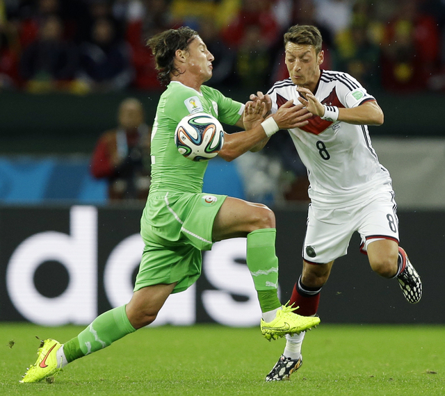 Algeria's Mehdi Mostefa, left, pushes off Germany's Mesut Ozil to stop his attack during the World Cup round of 16 soccer match between Germany and Algeria at the Estadio Beira-Rio in Porto Alegre ...