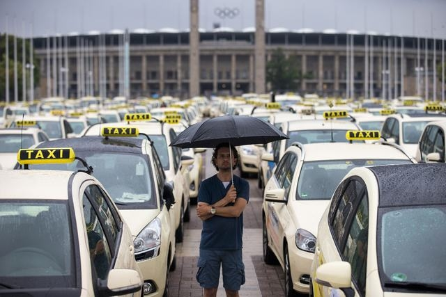 A man attends a Europewide protest of licensed taxi drivers in front of the Olympic stadium in Berlin on Wednesday, June 11, 2014. The protest denounce taxi hailing apps, such as Uber, that are fe ...