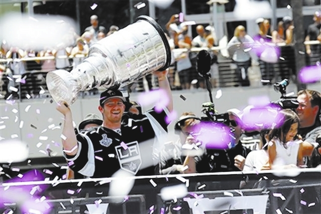 Los Angeles Kings goalie Jonathan Quick holds the Stanley Cup during a Monday parade in Los Angeles. Nearly two dozen members of the NHL champs celebrated Thursday at the MGM Grand's Crush resta ...
