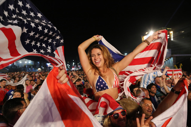 Fans of the U.S. national soccer team celebrate their team's victory during a live broadcast of the soccer World Cup match between the Unites States and Ghana, inside the FIFA Fan Fest area on Cop ...