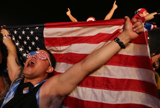 A soccer fan of the U.S. national soccer team celebrates his team's victory during a live broadcast of the soccer World Cup match between the Unites States and Ghana, inside the FIFA Fan Fest area ...