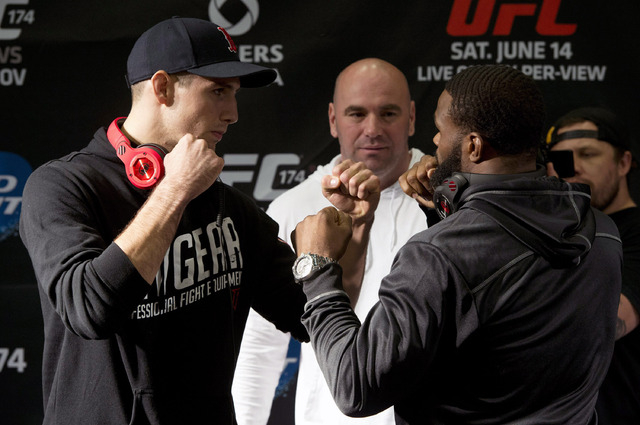 Rory MacDonald of Canada, left, and Tyron Woodley of the United States pose during their faceoff at EA Sports in Burnaby, British Columbia, Thursday, June, 12, 2014. The two will fight in UFC 174  ...