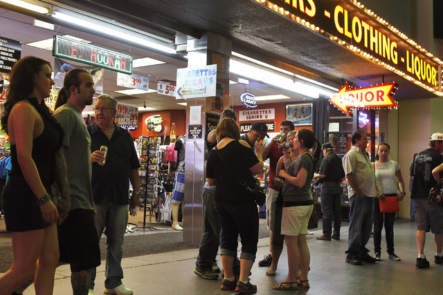 People hangout with their drinks that they purchased from a convenience shop at the Fremont Street Experience in Las Vegas on Thursday, May 22, 2014. Las Vegas City Council approved a liquor ordin ...