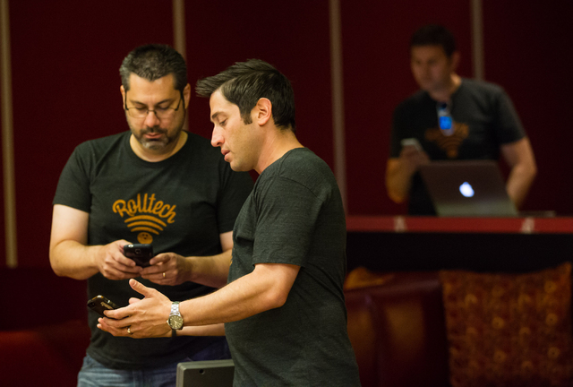 Rolltech CTO Rick Duggan, left, talks with founder and CEO Rich Belsky as the company runs tests for their bowling app. (Chase Stevens/Las Vegas Review-Journal)