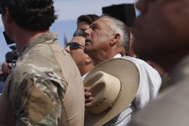 Surrounded by security personnel, rancher Cliven Bundy, middle, sings the National Anthem outside of Bunkerville while gathering with his supporters to challenge the BLM on April 12, 2014. (Jason  ...