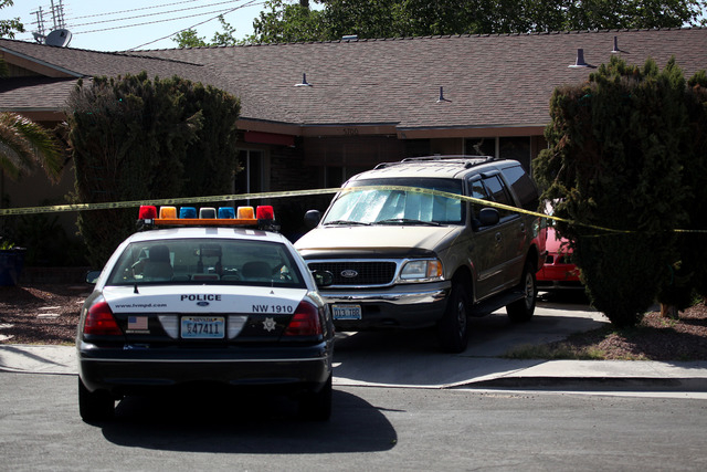 A Las Vegas Metropolitan police car sits parked outside the home where a shooting occurred on Cabrillo Circle in Las Vegas on Tuesday, June 17, 2014. (Justin Yurkanin/Las Vegas Review-Journal)