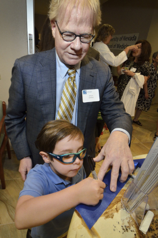Dr. Bill Zamboni watches as his son Nicolas signs the ribbon used for a ribbon cutting during the grand opening of the Patient Care Center operated by the University of Nevada School of Medicine a ...