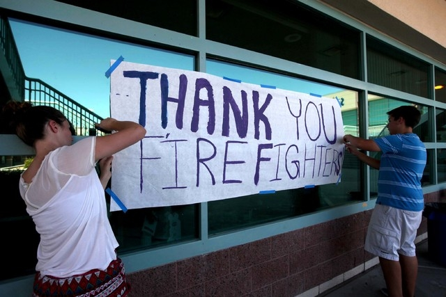 Centennial High School student council members Bridgett Bevilacqua, left, and Dylan Sacenti, both 17-year-old seniors, tape up a sign of support for firefighters at Centennial High School, the Car ...