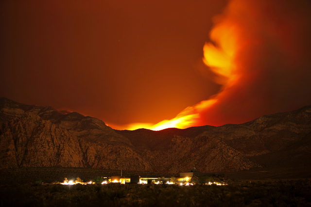 The Carpenter 1 Fire burns in the mountains behind the Red Rock Conservation Area visitor center near Las Vegas early in the morning of Thursday, July 11, 2013. The fire has forced the closure of  ...