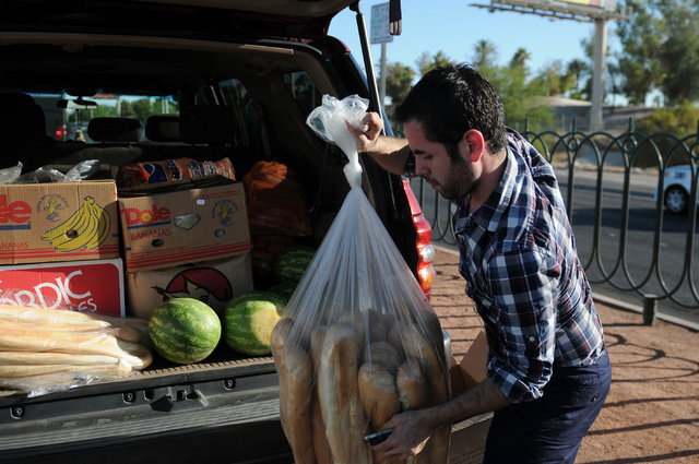 """Jesus Reyes, spokesman for Ringling Bros. and Barnum & Bailey circus, unloads loafs of breads for their elephants Kelley Ann and Bonnie during a welcoming event at the """"Welcome to Fabulous La ..."""