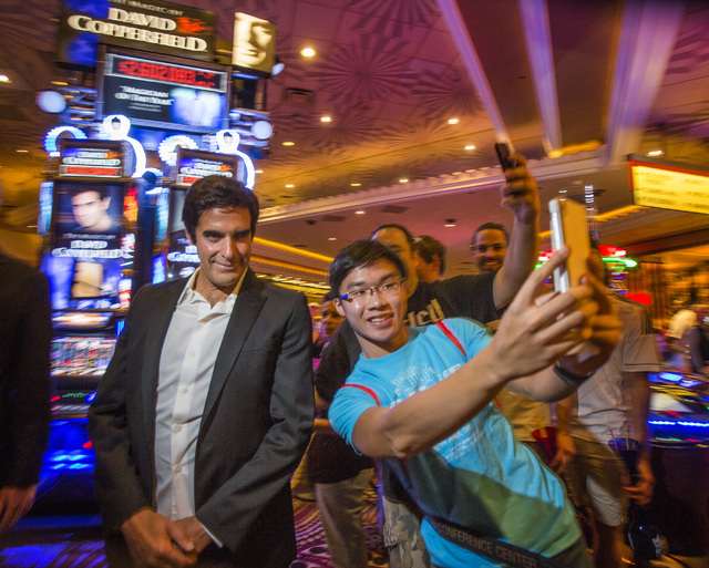 David Copperfield poses for a photo with a fan during the unveiling of slot machine with his namesake at MGM Grand on Thursday, June 26, 2014. The progressive slot machine is Bally Technologies' l ...